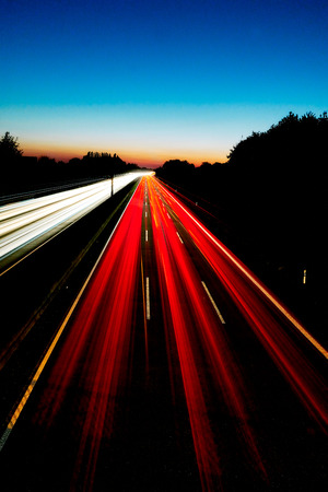 Vertical Long exposure image of the highway A2 in Germany Gelsenkirchen with red and white light trails and a colorful sunset in the background Stock Photo