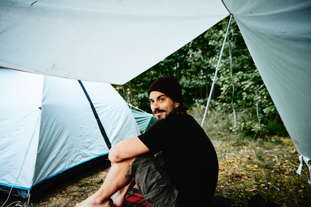 Young man with beard and barefoot sitting under a tarp next to a tent at a campground in a forest in Sweden waiting for the rain to stop. Man sits sideways and looks to the left into the camera with a smile.