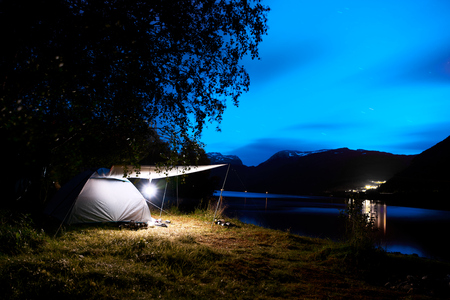 Camping with a illuminated tent at the beach and fjord in the mountains of Norway during night with a cloudy blue sky and stars. Stock Photo
