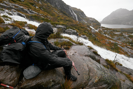 Hiking young man is sitting on a rock at the cliff edge with a backpack in the mountains next to a waterfall on the Lofoten Islands in Norway during a rainy day