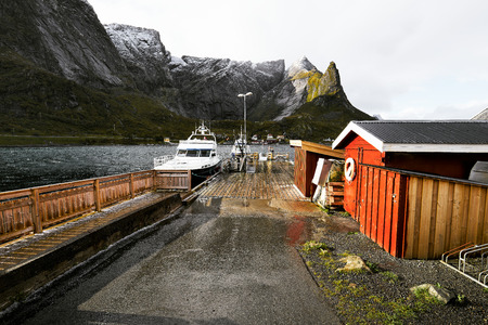 Scenic view of the harbor in Reine with a boat and the jetty at the coast on Lofoten Islands in Norway. The harbor is also the ferry station for tourists to be driven to Vinstad and Bunes Beach.