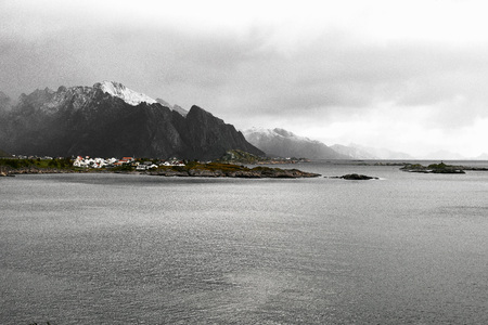Panoramic view of the norwegian coast and a village in front of a snowcapped mountain range during winter on Lofoten Islands in Norway. Stock fotó