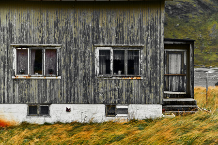 Old damaged wooden norwegian house with a red corrugated iron rooftop at Vinstad Village on Lofoten Islands in Norway.