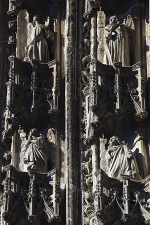 Figures carved in stone adorn the archway above the main entrance to St Gatien cathedral. Stock Photo - 14635429