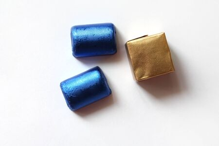 Chocolate candies wrapped in blue and golden foil isolated on white surface. Template for greeting card, poster or invitation. Sweets scattered on white smooth table. Backdrop or background