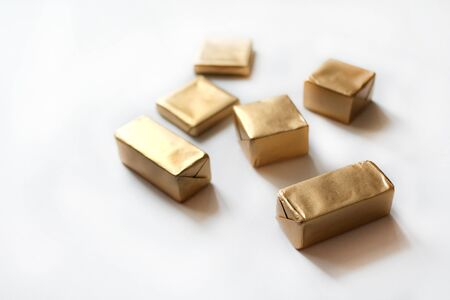 Chocolate candies wrapped in golden foil isolated on white surface. Template for greeting card, poster or invitation. Sweets scattered on white smooth table. Backdrop or background