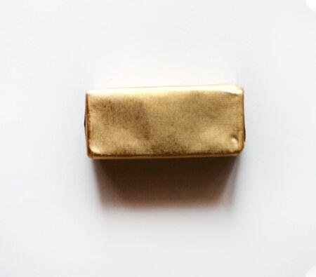 Caramelo de chocolate rectangular envuelto en papel azul aislado en la superficie blanca. Objeto para tarjeta de felicitación, póster o invitación. Telón de fondo o fondo