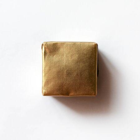 Caramelo de chocolate cuadrado envuelto en papel azul aislado en la superficie blanca. Objeto para tarjeta de felicitación, póster o invitación. Telón de fondo o fondo Foto de archivo