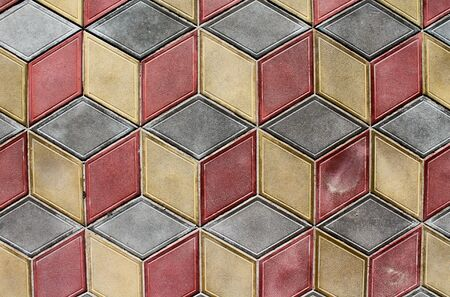 Colorful geometric tiles on the ground. Diamond shaped tiles of gray, yellow and red colors. Abstract background with cubes pattern