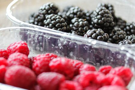 Background with fresh berries in plastic boxes closeup. Blackberry and raspberry macro photography. Organic berries of black and red color. Template for menu, organic shop, harvesting. Healthy eating