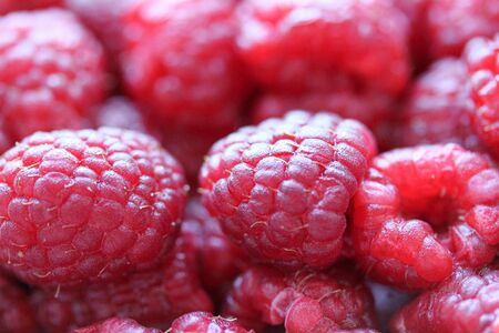 Background with fresh raspberry closeup. Raspberry macro photography. Organic berries of bright red color. Template for banner, menu, food label, organic shop, garden harvesting. Healthy eating