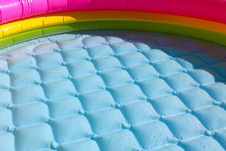 Bright blue inflatable paddling pool surface with water ripples. Summer picture of swimming pool with green, yellow and pink side. Background or backdrop