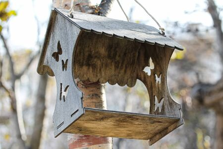 Wooden carved birdfeeder for birds and animals in the city park. Carved butterflies and roof. Bird house hanging on the tree