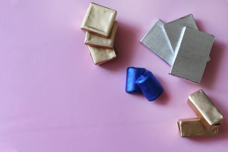 Pile of chocolates wrapped in silver, golden and blue foil. Copy space for text. Template for greeting card, poster or invitation. Sweet candies on pink smooth table. Backdrop or background