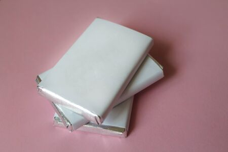 Pile of chocolates wrapped in silver foil and white blank paper. Copy space for text. Template for greeting card, poster or invitation. Sweet candies scattered on pink smooth table. Backdrop or background