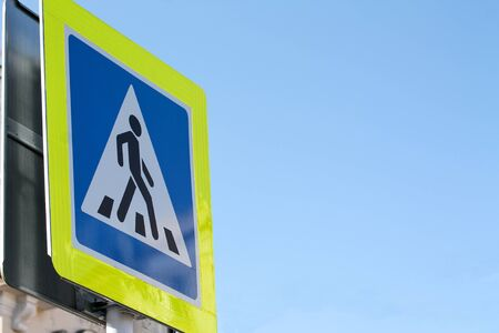 Pedestrian crossing blue sign with yellow light-reflecting frame. Blue sky background with copy space for text. Picture of person crossing the road. Road laws and highway regulations