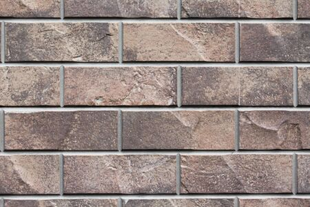 Brown stone siding tile wall abstract background. House exterior with blocks. Crafted outer wall Stock Photo