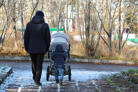 Young kid walking with his father and sibling in the stroller. Man and his son on a walk in the autumn park. Cute picture of toddler boy pushing a stroller with his brother or sister. Family love
