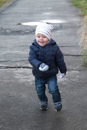 Funny toddler boy running on a walk in autumn. Smiling child wearing white hat, blue jacket, woolen mittens and jeans on sidewalk. Happy kid portrait