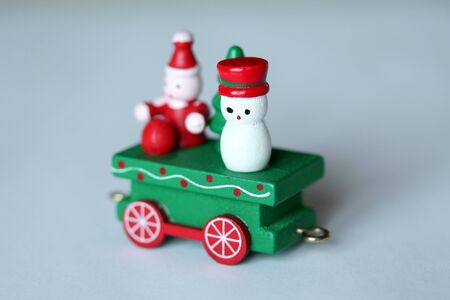 Green festive wooden train car or carriage on white background. Christmas and New Year toy with figures of snowman, gnome and fir tree. Greeting card, poster template Stock Photo