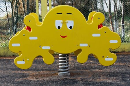 Spring swing with funny wooden octopus on kids playground. Yellow swing with benches for two toddlers. Amusing attraction for children Banque d'images