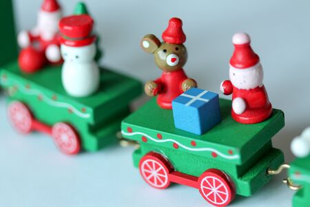 Green festive wooden train riding on white background. Selective focus on mouse or rat. Christmas and New Year toy with figures of snowman, gnomes. Greeting card, poster template