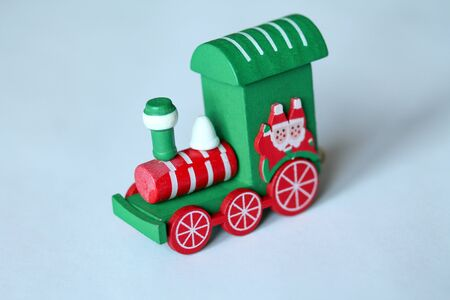 Green festive wooden train locomotive or railway engine on white background. Christmas and New Year toy with figures of waving santa or gnome. Greeting card, poster template