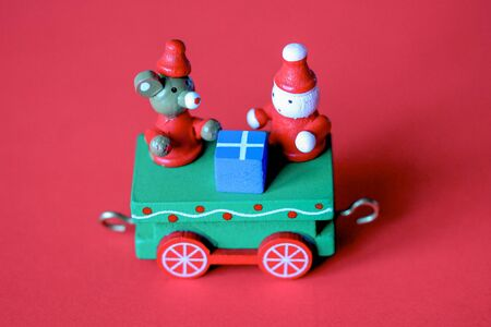 Green festive wooden train car or carriage on red background. Christmas and New Year toy with figures of mouse or rat, gnome and gift box. Greeting card, poster template