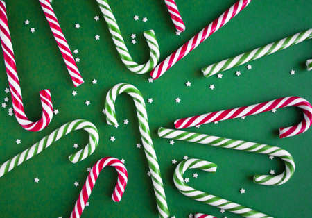 Christmas background with candy canes. Red and green sweet sticks with small stars. Flat lay, overhead view. Poster, banner, greeting card template. Festive backdrop. Holiday season