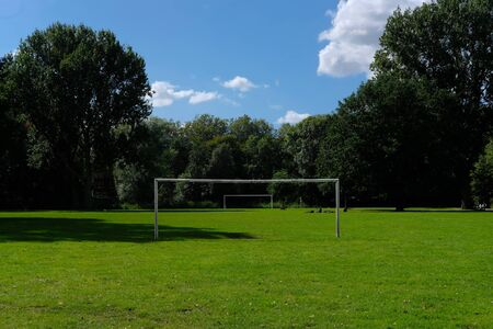 Two football or soccer goalposts in parallel in a park with green grass and blue skies and people sitting in the grass Imagens