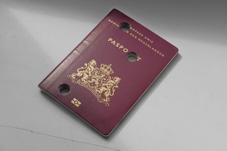 A Dutch passport made unusable with perforations on a plain background