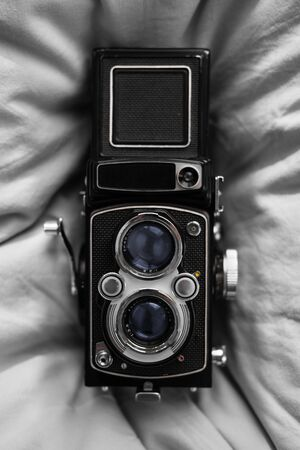 An old twin reflex camera on a soft background