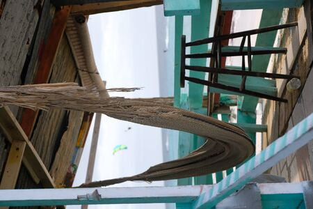 A hammock in an abandoned beach shack with a bar stool Imagens