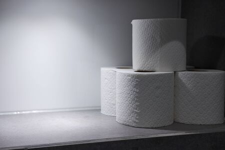 Toilet rolls in a recess in the wall with top lighting close up