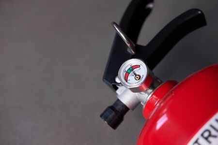 Fire extinguisher barometer close up with grey background
