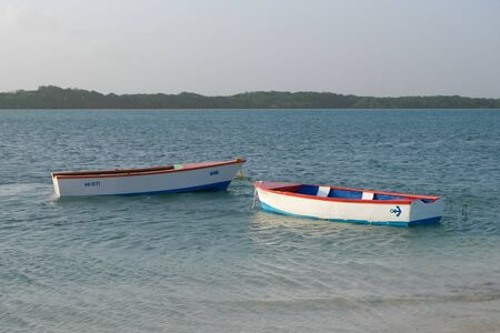 Two blue white red rowing boats floating near the beach Imagens