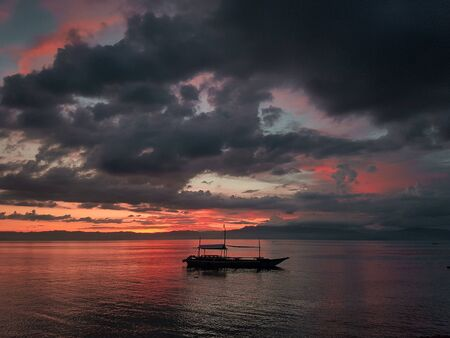 Traditional Philippines boat floating in the water at fire red sunset