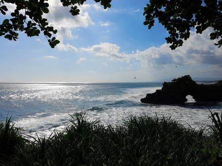 Waves rolling in at Tanah Lot temple Bali with birds flying past