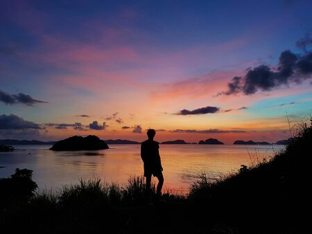 Male standing on a hill looking at a colorful sunset in El Nido in the Philippines