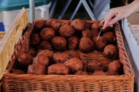 Deep fried donut balls commonly eaten on new years eve with hand holding fork