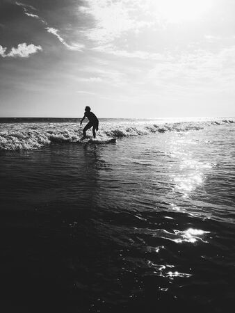 Male surfing white wash waves in Bali in black and white colors Stock Photo