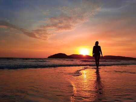 Female walking in shallow sea water at sunset