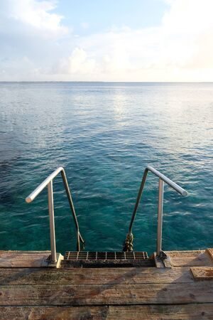Old metal swimming ladder with blue tropical waters Imagens