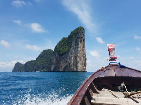Traditional Thai boat driving towards a large island in the sea with waves crashing