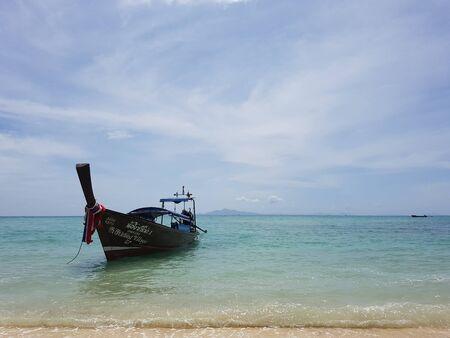Traditional Thai boat on anchor near the beach coast in Thailand
