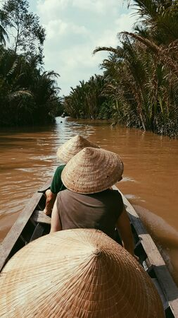Three people wearing Asian conical hats in a small wooden boat rowing down a brown river delta surrounded by large plants