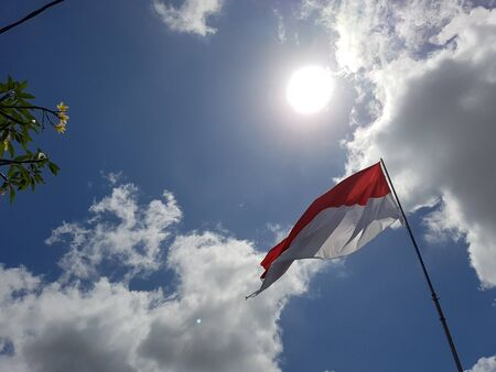 Indonesia flag waving in the wind against the bright sunny and partially cloudy sky 版權商用圖片
