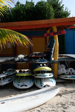 Wind surfboards stacked on top of each other in the sand