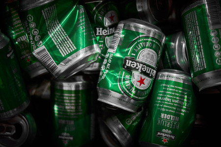 Many Heineken beer cans crumbled up in a trash can close up Editorial