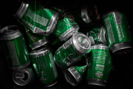 Many Heineken beer cans crumbled up in a trash can